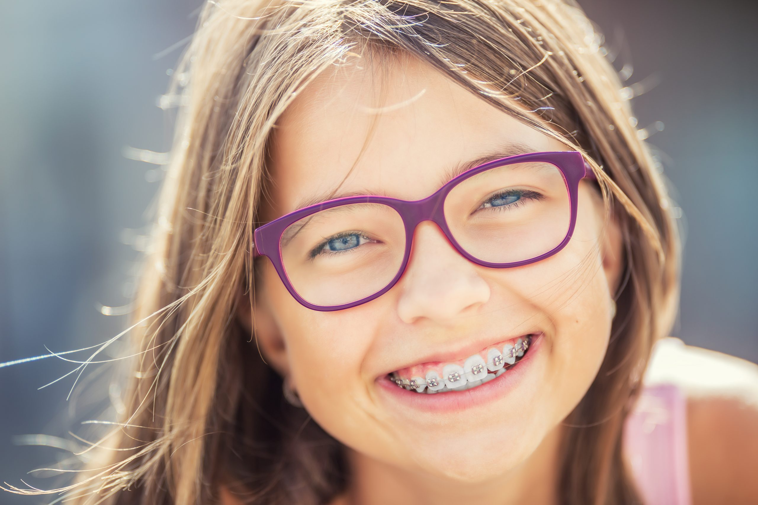 Happy smiling girl with dental braces and glasses. Young cute caucasian blond girl wearing teeth braces and glasses